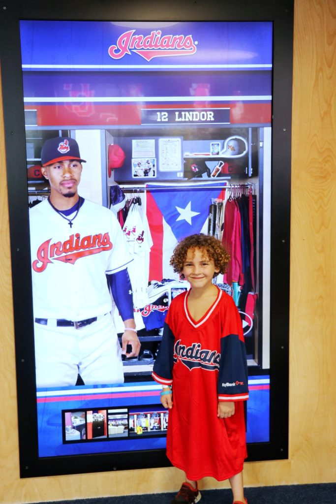 kid wearing a one-size fits all freebie francisco lindor mr. smile jersey at the cleveland indians game