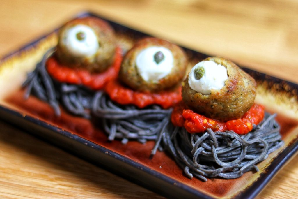 easy halloween food ideas: eyeball meatballs spooky spaghetti with black bean noodles