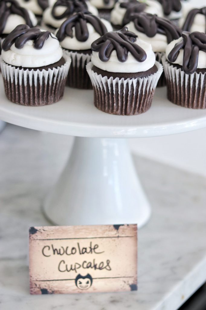 dessert idea for a bendy and the ink machine birthday party: chocolate cupcakes with white frosting and black candy melt drips